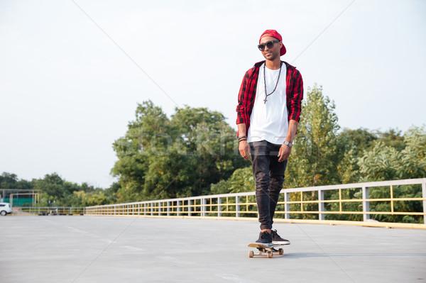 Dark skinned man wearing sunglasses and cap skateboarding Stock photo © deandrobot