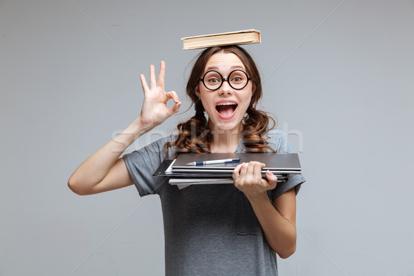 Funny Female nerd with book on head Stock photo © deandrobot