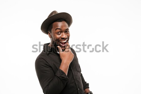 Cheerful young african man dressed in shirt wearing hat Stock photo © deandrobot