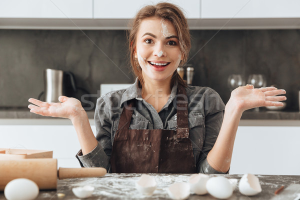 Smiling lady standing in kitchen while cooking Stock photo © deandrobot