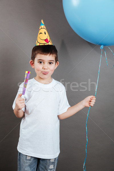 Little boy in birthday hat showing toungue and celebrating Stock photo © deandrobot