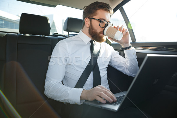 Bearded business man using laptop and drinking coffee Stock photo © deandrobot