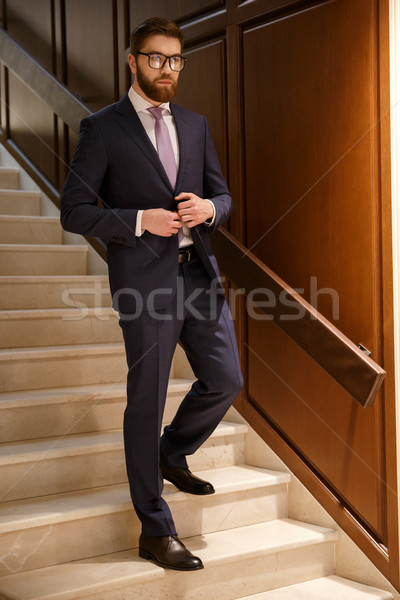 Serious young bearded businessman standing on ladder indoors. Stock photo © deandrobot