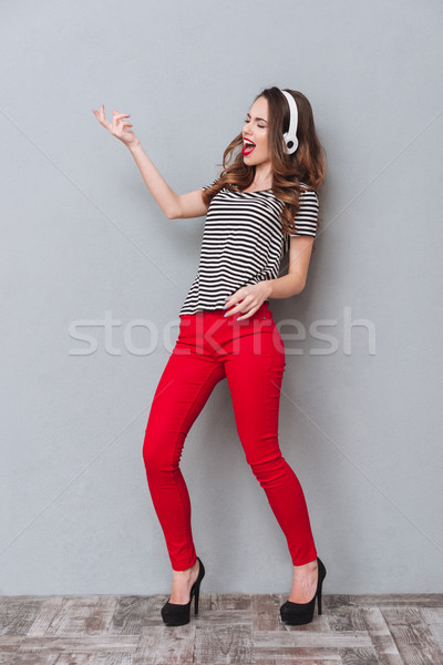 Full length portrait of woman listening music and playing guitar Stock photo © deandrobot