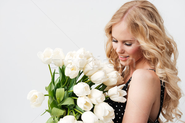 Vista lateral sonriendo mujer rubia posando ramo flores Foto stock © deandrobot
