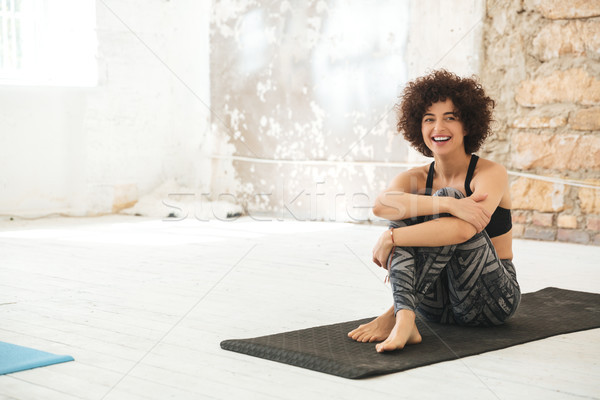 Happy young woman sitting in yoga studio Stock photo © deandrobot