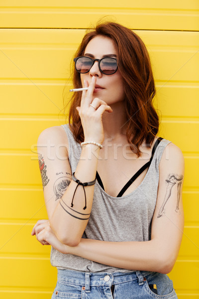 Young woman with cigarette standing over yellow wall. Stock photo © deandrobot