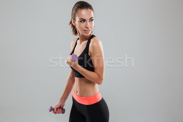 Side view of sports woman doing exercise with dumbbells Stock photo © deandrobot