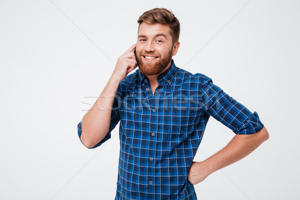 Smiling bearded man in checkered shirt talking by the smartphone Stock photo © deandrobot