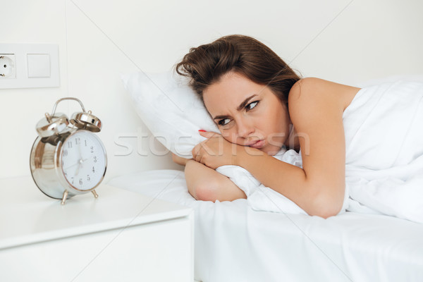 Angry irritated woman laying in bed in the morning Stock photo © deandrobot