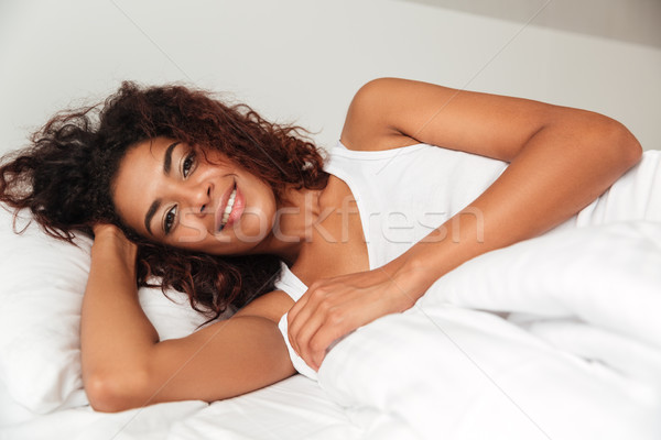 Pretty woman lying in bed with pillow and looking camera Stock photo © deandrobot