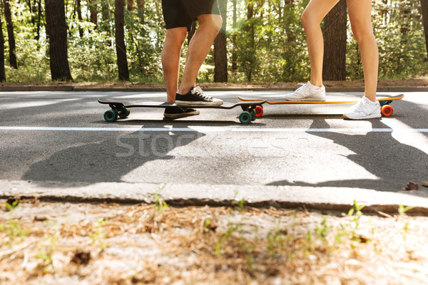 Cropped image of young loving couple on skateboards. Stock photo © deandrobot