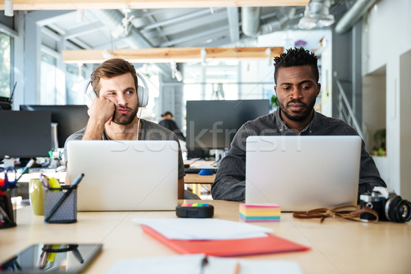 Confused young colleagues sitting in office coworking Stock photo © deandrobot