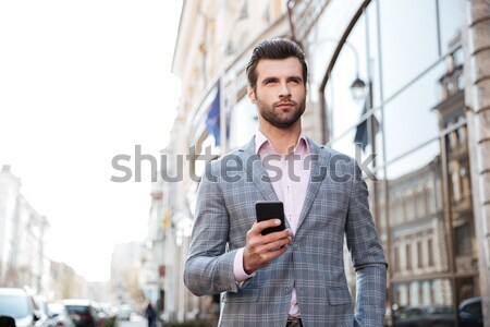 Concentrated young businessman outdoors chatting Stock photo © deandrobot