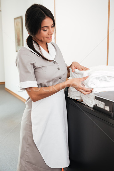 Smiling maid taking fresh towels from a housekeeping cart Stock photo © deandrobot