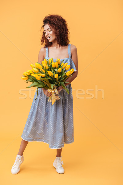Full-length portrait of Smiling African woman holding bouquet  f Stock photo © deandrobot