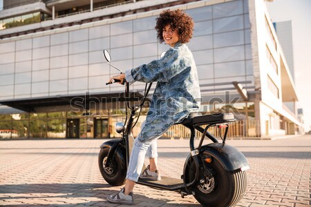Full length side view of pleased curly woman sitting on motorbik Stock photo © deandrobot