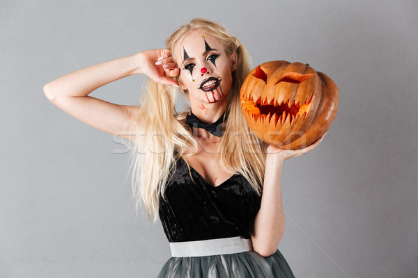 Young blonde woman in halloween make-up posing with carved pumpkin Stock photo © deandrobot