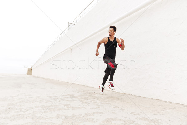 Happy african sports man running outdoors. Stock photo © deandrobot