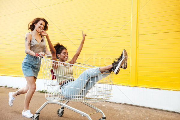 Smiling women friends have fun with shopping trolley. Stock photo © deandrobot