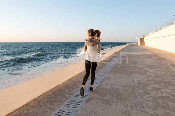 Back view of young slim fitness woman running at seaside Stock photo © deandrobot