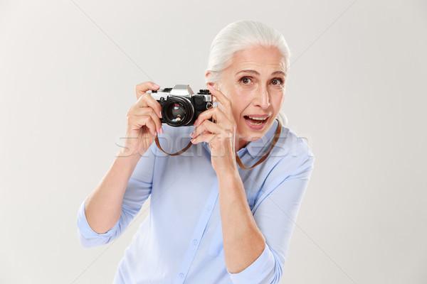 Happy mature woman holding retro camera isolated over white Stock photo © deandrobot