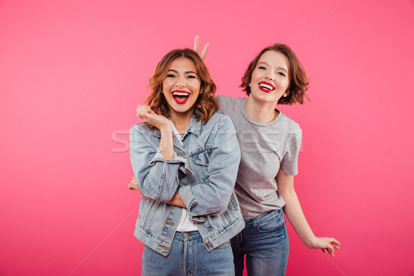 Two ladies friends standing isolated have fun. Stock photo © deandrobot