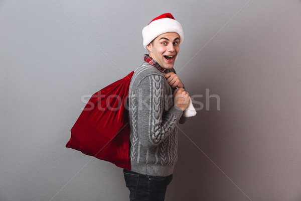 Side view of happy man in sweater and christmas hat Stock photo © deandrobot