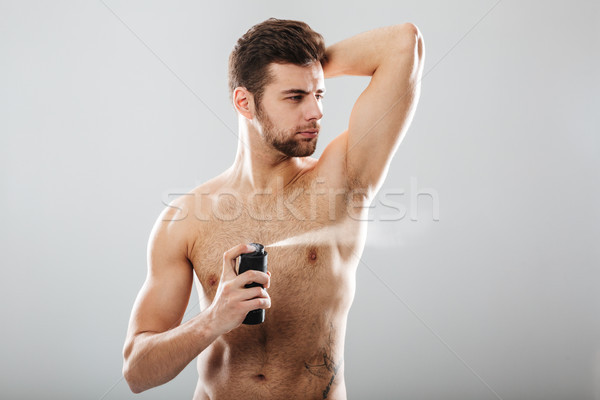 Portrait of handsome shirtless guy spraying perfume over his mus Stock photo © deandrobot