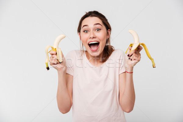 Portret vrolijk jong meisje eten bananen naar Stockfoto © deandrobot