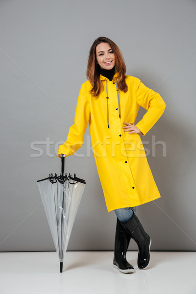 Full length portrait of a smiling girl dressed in raincoat Stock photo © deandrobot