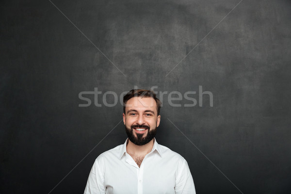 Cropped portrait of young joyful man in white shirt posing on ca Stock photo © deandrobot
