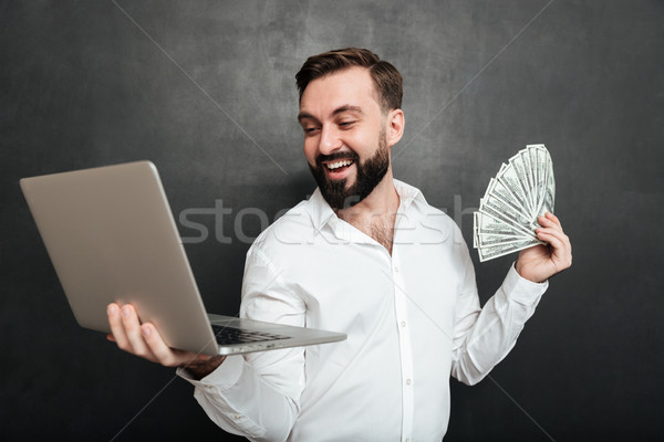 Portrait of successful businessman in white shirt holding fan of Stock photo © deandrobot