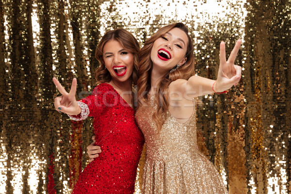 Portrait of two excited cheery women in sparkly dresses Stock photo © deandrobot