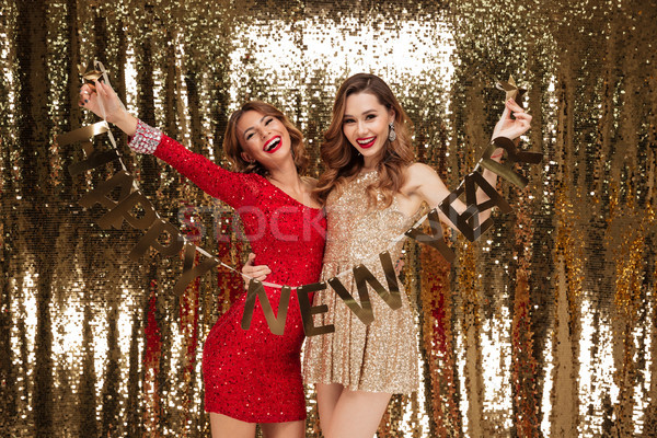 Portrait of two excited attractive women in sparkly dresses Stock photo © deandrobot
