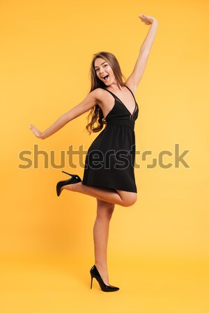 Pretty young woman in black dress standing isolated Stock photo © deandrobot