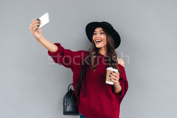 Portrait of a smiling young asian girl dressed in hat Stock photo © deandrobot