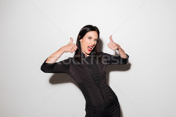 Portrait of a satisfied woman showing thumbs up gesture Stock photo © deandrobot