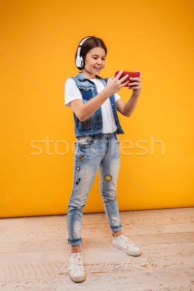 Ritratto felice piccolo studentessa ascoltare musica Foto d'archivio © deandrobot
