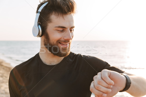 Close up of a handsome young sportsman in headphones Stock photo © deandrobot