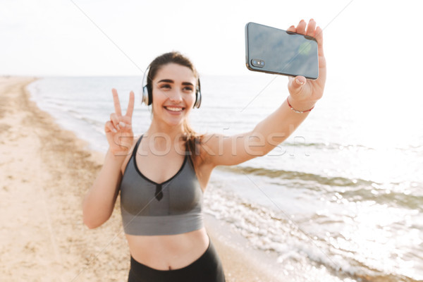 Smiling young sportswoman standing at the beach Stock photo © deandrobot