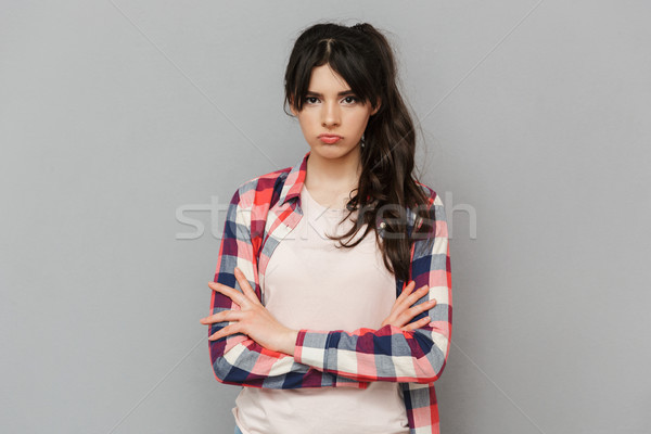 Displeased sad young lady standing isolated Stock photo © deandrobot