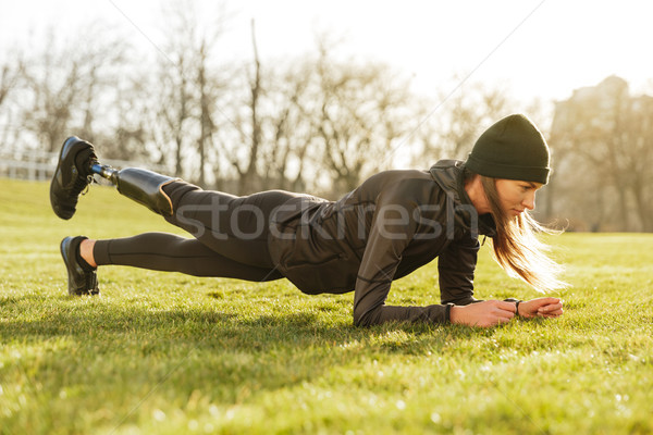 Image of sporty handicapped woman in black tracksuit, warming up Stock photo © deandrobot