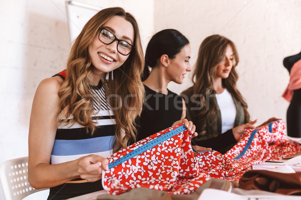 Three happy young women clothes designers Stock photo © deandrobot