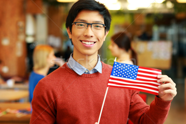 Smiling asian student holding flag of USA Stock photo © deandrobot