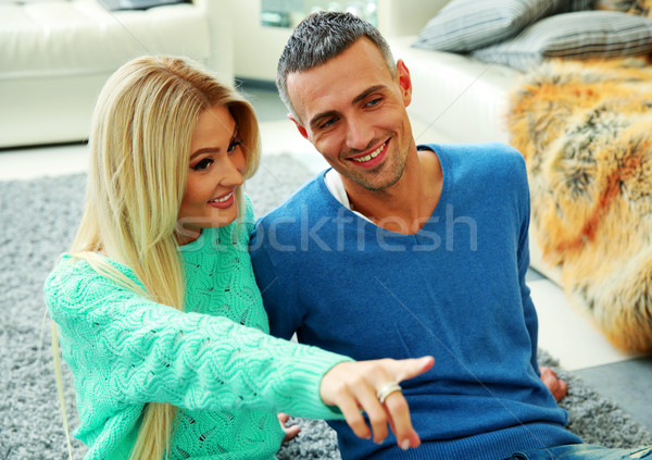 Happy couple sitting on floor at home Stock photo © deandrobot