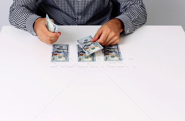 Portrait of businessman counting hundred dollar bills at desk Stock photo © deandrobot