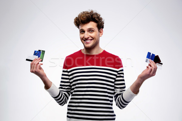 Happy casual man holding credit cards over gray background Stock photo © deandrobot