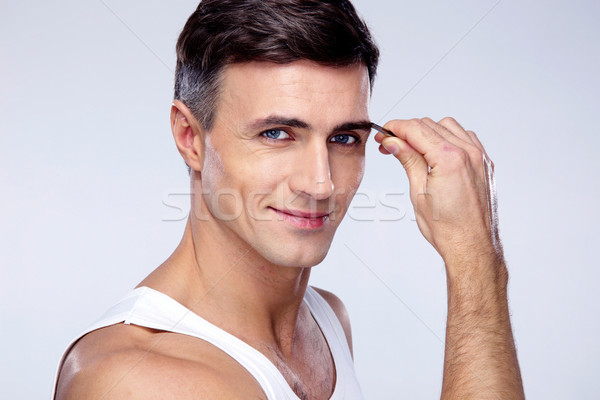 Happy man removing eyebrow hairs with tweezing Stock photo © deandrobot