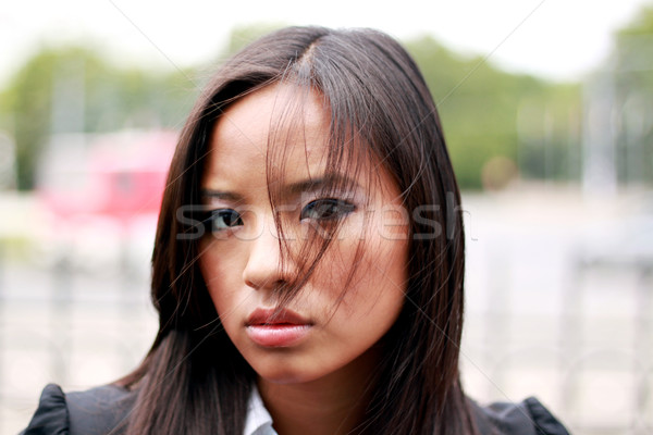 Thoughtful young beautiful asian businesswoman. Windy. Stock photo © deandrobot